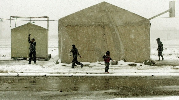 Syrian refugees play with snow