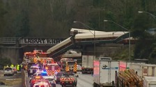 Train derails off bridge on to busy road near Seattle