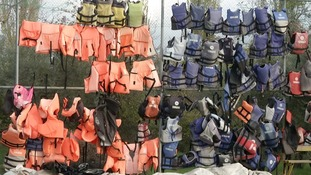 Life jackets hang on fencing as a reminder of the refugees' desperate escape.