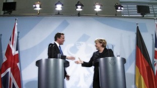 David Cameron shakes hand with German Chancellor Angela Merkel during a news conference
