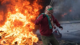A protester in Ramallah, Palestine, about to launch a projectile at Israeli forces.