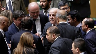 Palestine's Dr. Riyad Mansour, center, talks with members of the UN General Assembly.