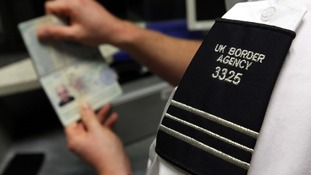 A UK Border Agency officer checks a passport in the North Terminal of Gatwick Airport, Sussex.