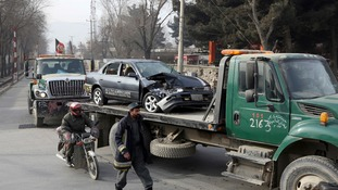 Afghan security forces remove a destroyed vehicle after the suicide attack in Kabul