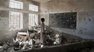 A student stands in a classroom in Yemen that was destroyed in an attack.