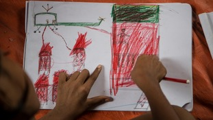 A Rohingya child works on a drawing of a helicopter attacking homes.