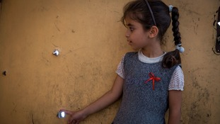 'Our house has these too,' says an Iraqi child looking at bullet holes in a door.