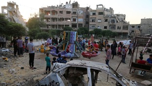 Children play among the ruins of bombed out building and cars in Syria.