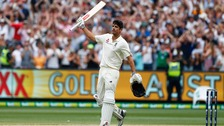 Alastair Cook raises his bat at the MCG after hitting a double century.