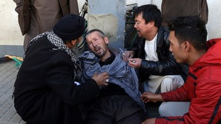 A distraught man is cared for outside a hospital following the suicide attack in Kabul.