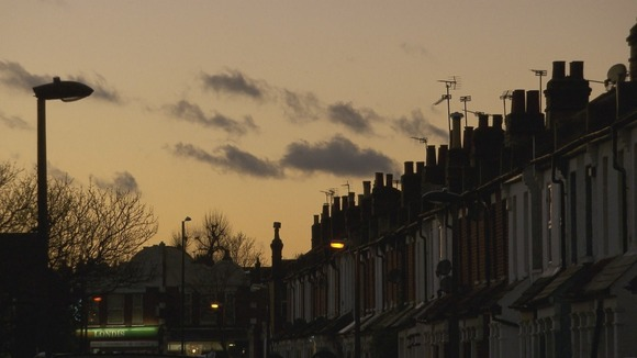 Row of terraced houses set against sky at dusk