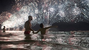 People watch fireworks over Copacabana beach in Rio, Brazil.