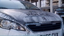 A police car is covered in ash from the major fire at a car park in Liverpool