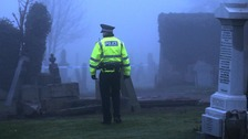 Police look on as the grave is refilled this afternoon.