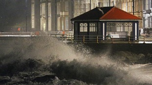 Waves crash against the sea wall in Aberystwyth in west Wales.