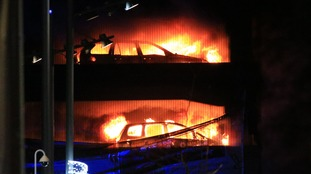 Blazing vehicles can be seen in the car park fire.