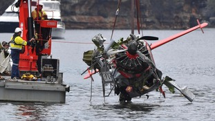 Workers lift part of the wreckage from the water.