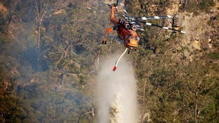 An Air-Crane Helitanker dumps water on a fire near Marulan, which is located around 87 miles from south west Sydney.