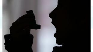 An asthma sufferer using an inhaler.