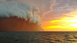 A cloud formation tinged with red dust travelling across the Indian Ocean