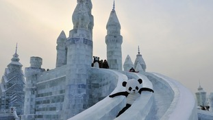 An employee wearing a panda costume slides down from an ice sculpture