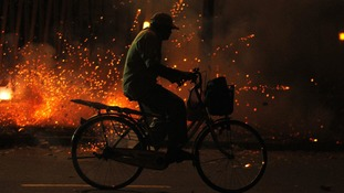 A man rides his bicycle as firecrackers are lit in celebration