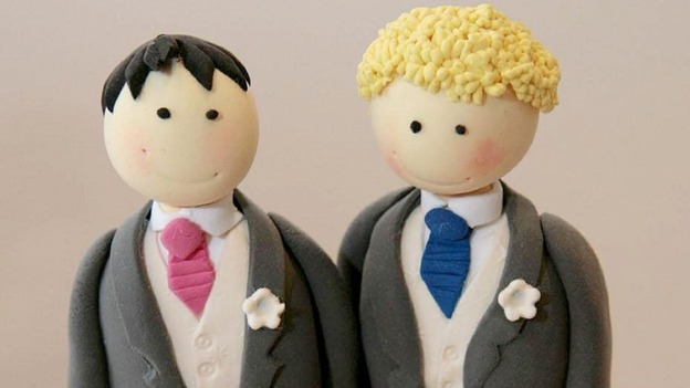 A wedding cake topper for a civil partnership with two men.