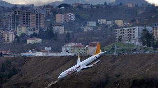 Plane left dangling on cliff face metres from the sea after skidding off runway