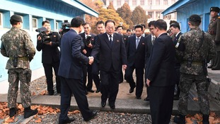 The head of North Korean delegation Jon Jong Su, centre, is greeted by a South Korean official as he crosses a border.