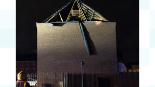 The gable end of a roof was blown away from a house