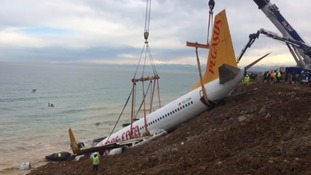 Plane hauled back to safety after skidding off runway and down shallow cliff face