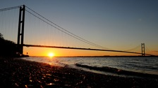 The sun rises behind the Humber Bridge.