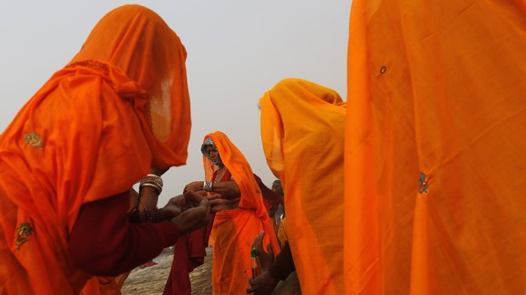 Hindus apply oil on bodies after taking holy dip in the River Ganges ahead of the festival