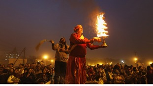 A Hindu priest holds oil lamp as performs evening prayers near the banks of the River Ganges