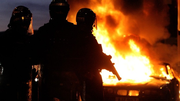 Riot police stand next to a burned out car in east Belfast