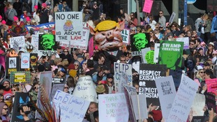 Demonstrators hold placards at a women's march in Los Angeles.