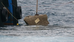 The memorial plaque affixed to the last piece of rock to be removed from the Costa Concordia.