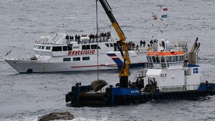 Workers drop a stone with a plaque into the sea during a ceremony to commemorate the first anniversary of the Costa Concordia tragedy.