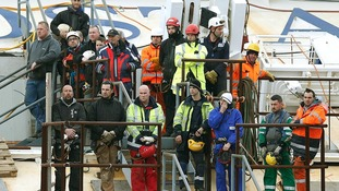 Salvage crew workers stand on a side of the capsized cruise liner Costa Concordia as they pay respects to the deceased