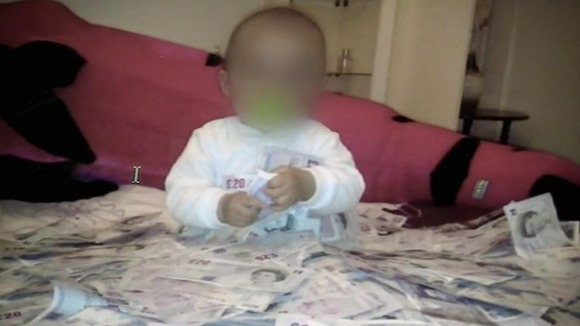 A photo seized by police of a baby surrounded by cash