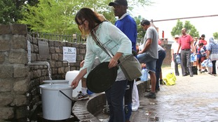 People in Cape Town queue for water.