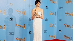 Anne Hathaway holds the award she won for Best Supporting Actress in Les Miserables