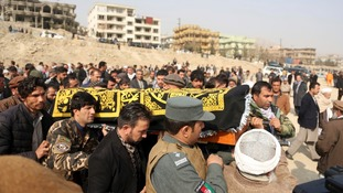 Mourners carry the coffin of one of the victims of the attack.