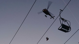 A skier is rescued from the chairlift.