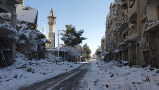 Snow covers buildings that activists say were damaged by missiles from Syrian Air Force planes in Daraya, near Camascus