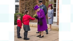 The Queen is presented with a posy of flowers by children from Cherry Tree Academy