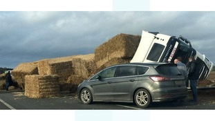 A lorry carrying hay bales has overturned on the A11