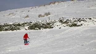 A woman pulls a sledge up a hill in Flash in Staffordshire.