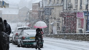 A woman is caught in a heavy snow shower in Pickering, North Yorkshire.