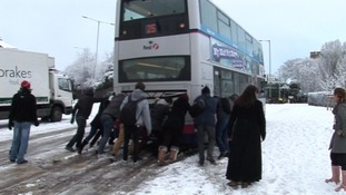 People help push a bus up Market Avenue in Norwich